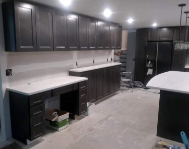In-progress kitchen remodel with new cabinets, granite countertops prior to backsplash installation